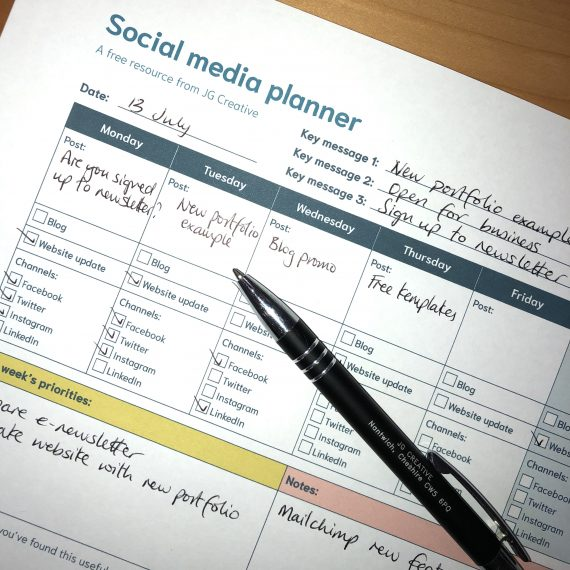 Photograph of a Social media planner filled out with a pen resting on top